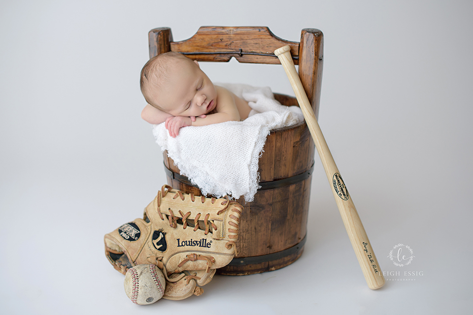 newborn boy with baseball mitt and bat