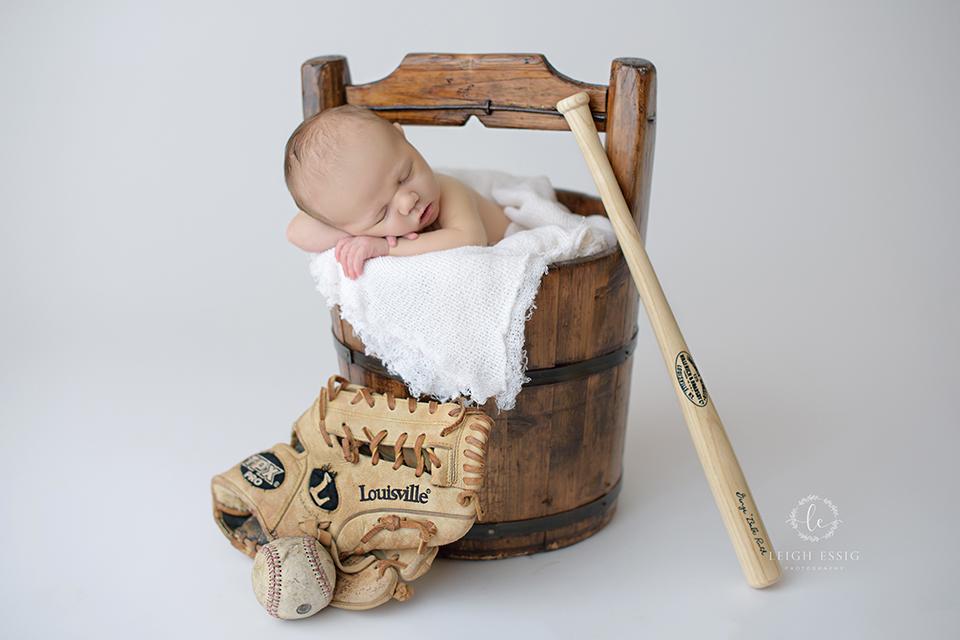 newborn boy with baseball mitt and bat