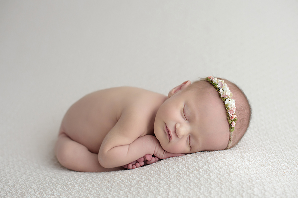 Naked newborn baby girl sleeping on cream backdrop
