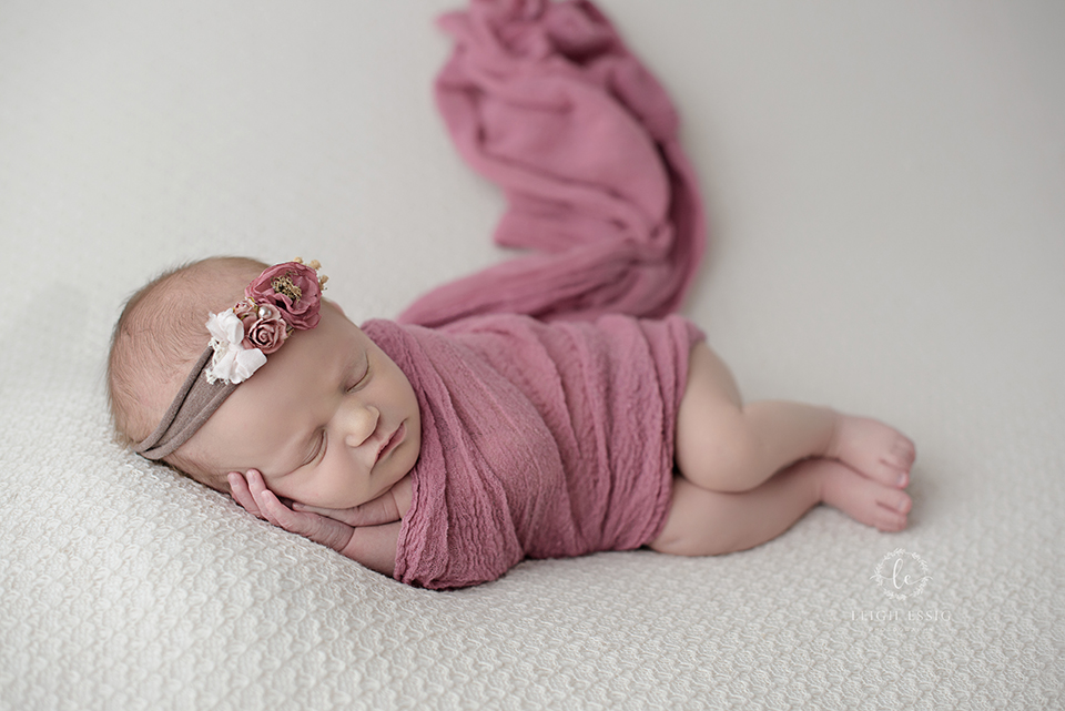 Newborn baby photographer- girl in mauve wrap and tie-back headband
