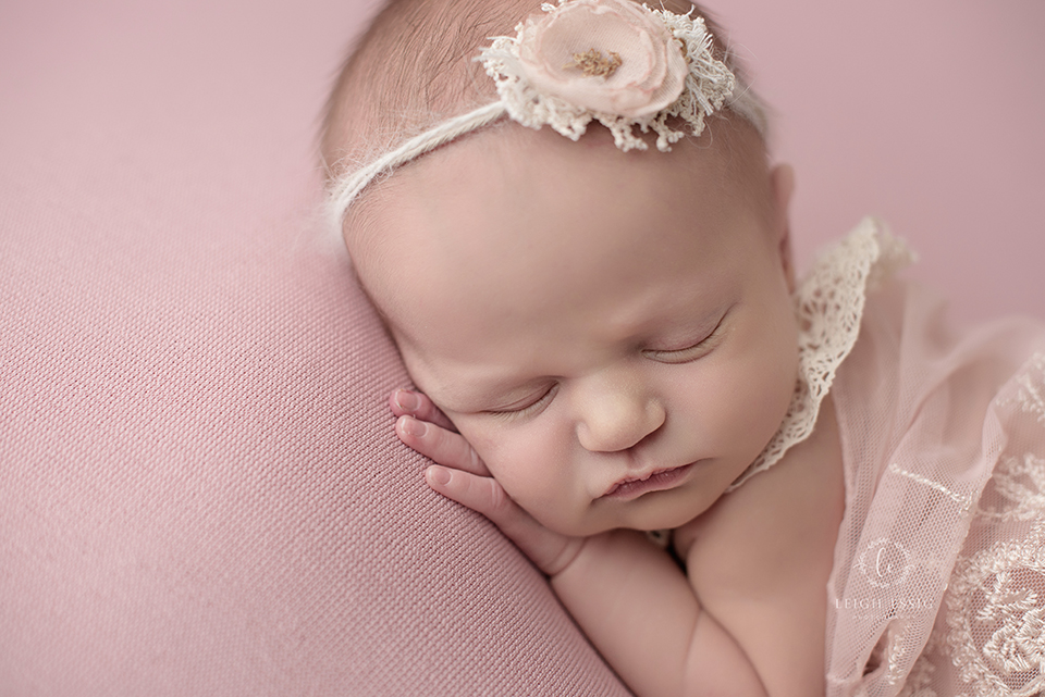 Baby girl on pink backdrop in pink lace and crochet outfit