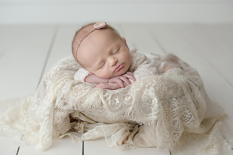 Newborn photography- baby girl with pink rosette headband on cream lace