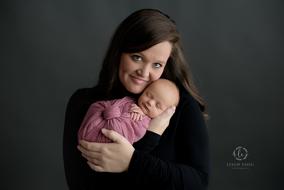 Mom holding sleeping newborn girl in mauve wrap
