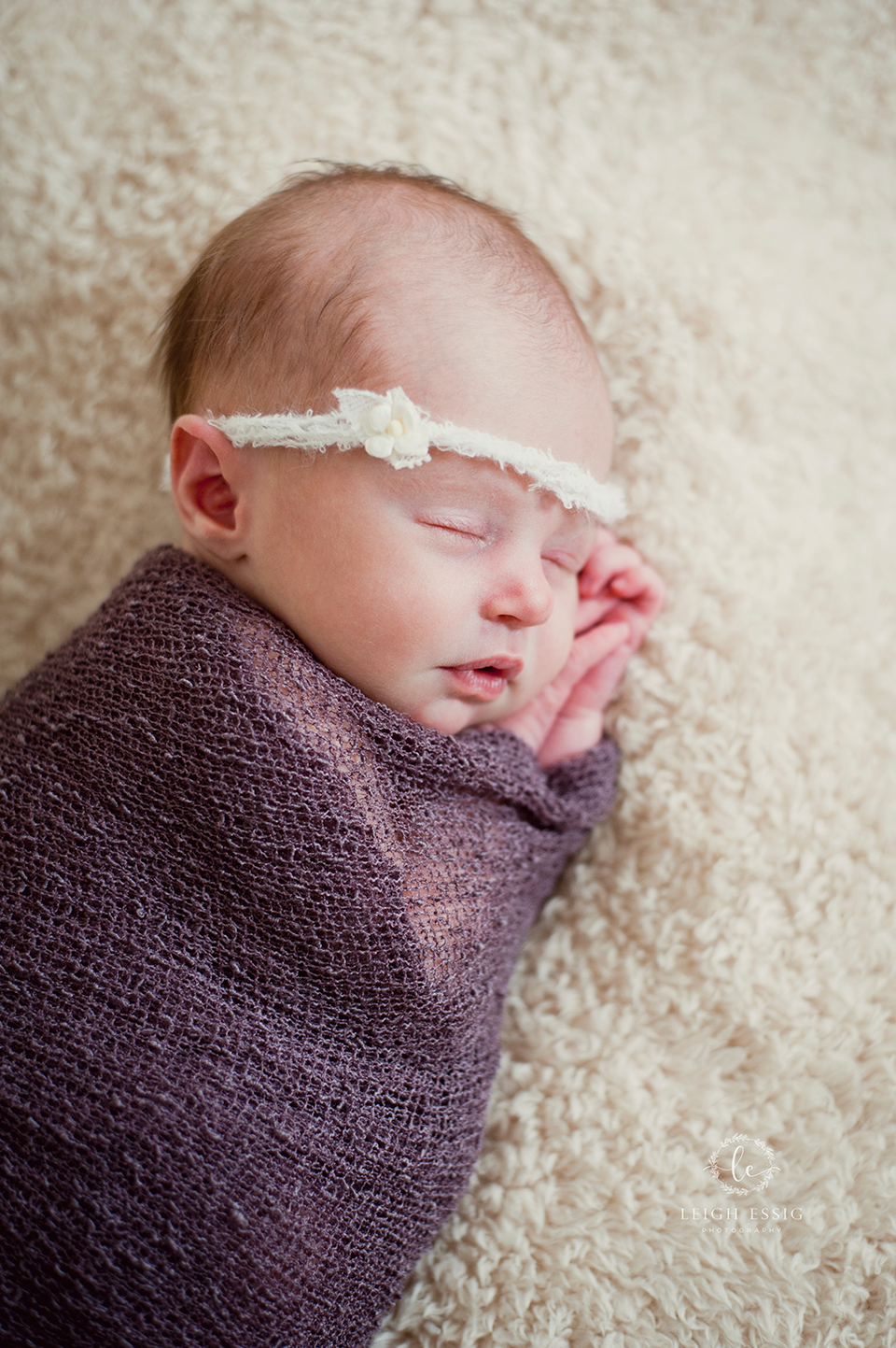 Baby girl sleeping with cream flower headband and purple wrap