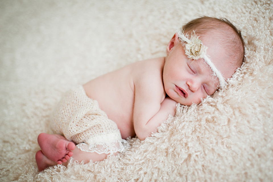 Newborn baby girl on cream backdrop in knit bloomers